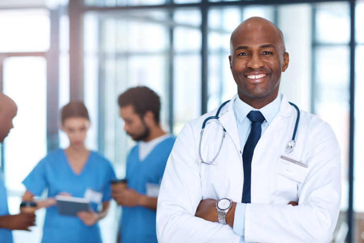 Portrait of a mature doctor standing in a hospital with his colleagues in the background